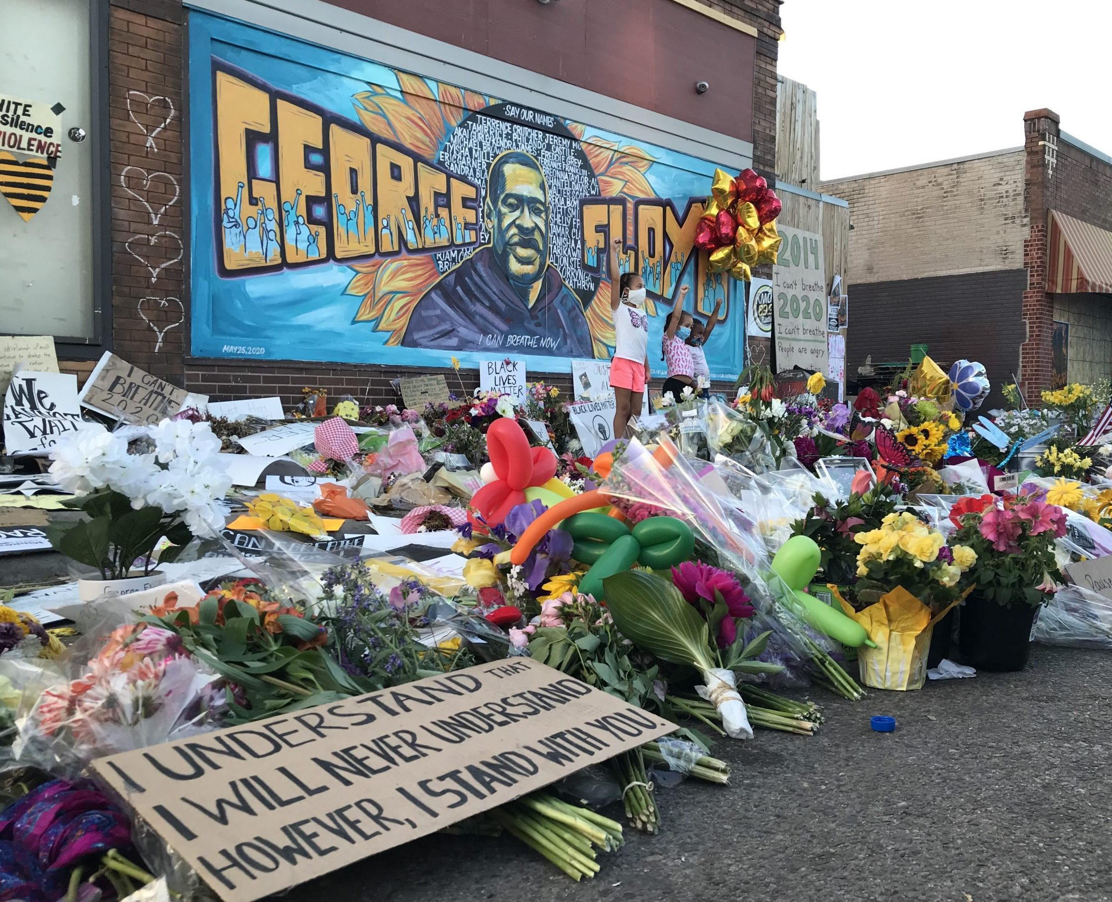 Tributes arranged before a mural of George Floyd on the side of Cup Foods in south Minneapolis, where Floyd was killed