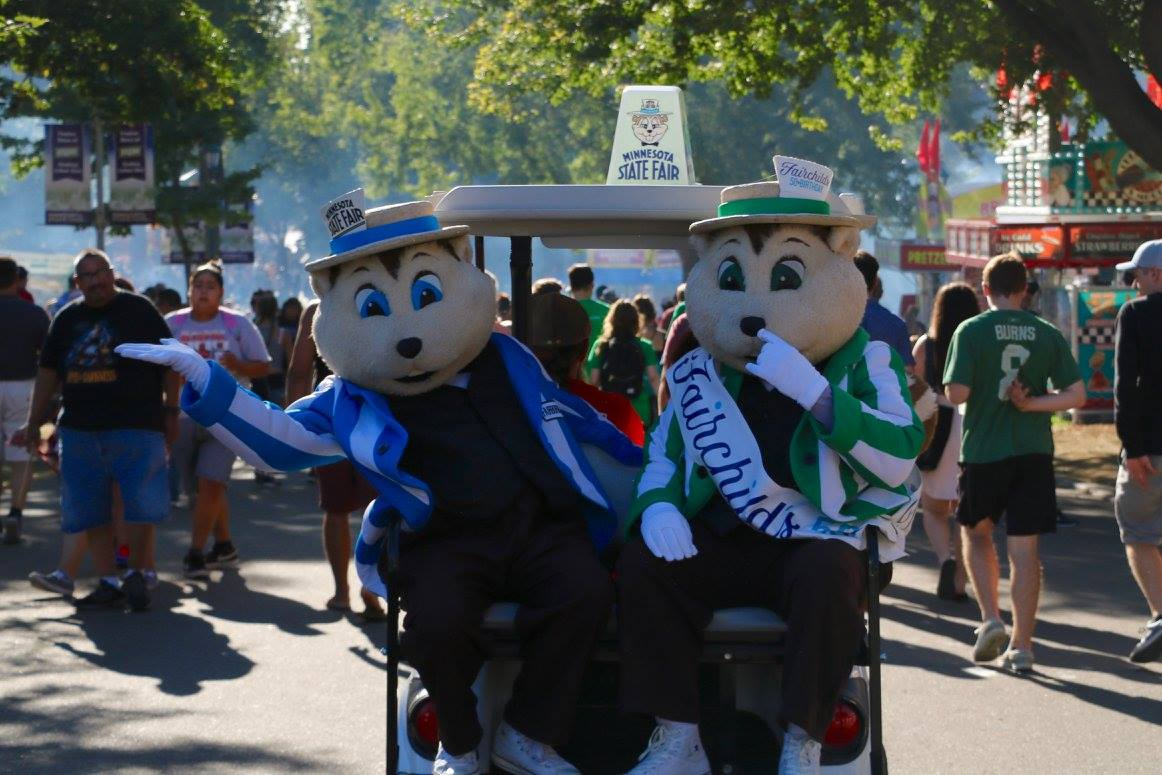 The two state fair mascots riding on a golf cart