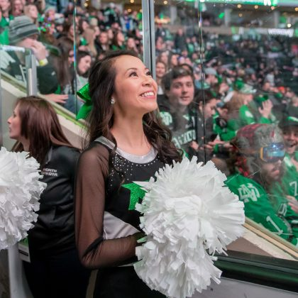 UND student Michelle Nguyen smiling and holding pom-poms at a hockey game