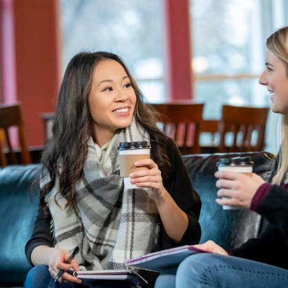 UND student Michelle Nguyen sitting on a couch, holding a coffee, and talking to another student