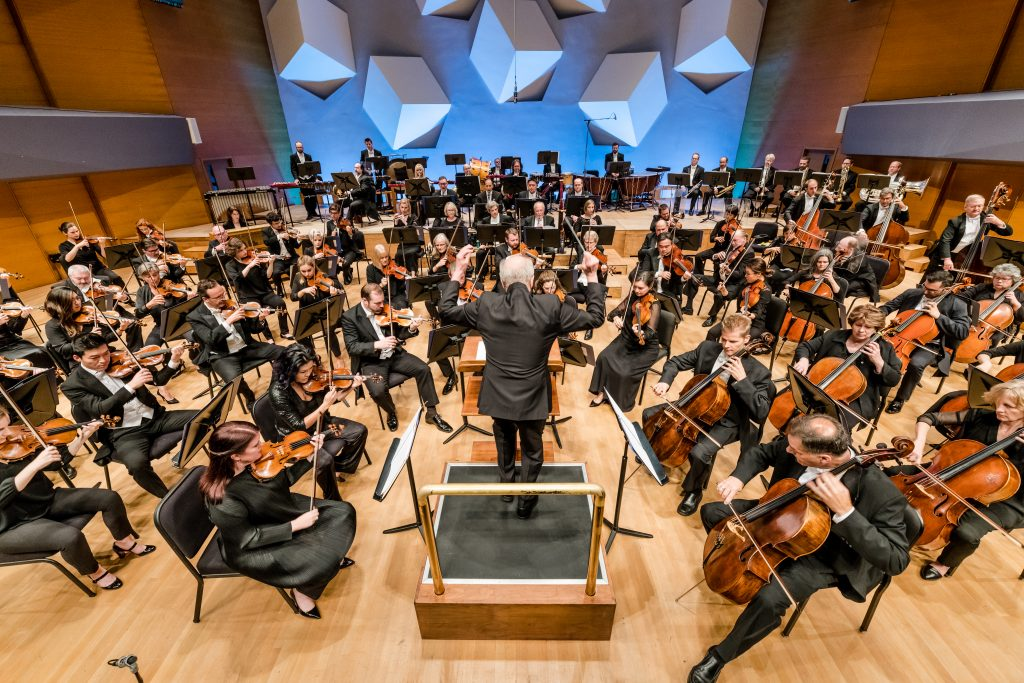 Minnesota Orchestra performers play on stage led by music director Osmo Vänskä