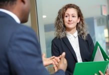 Woman wearing professional attire speaking with a businessman at EY
