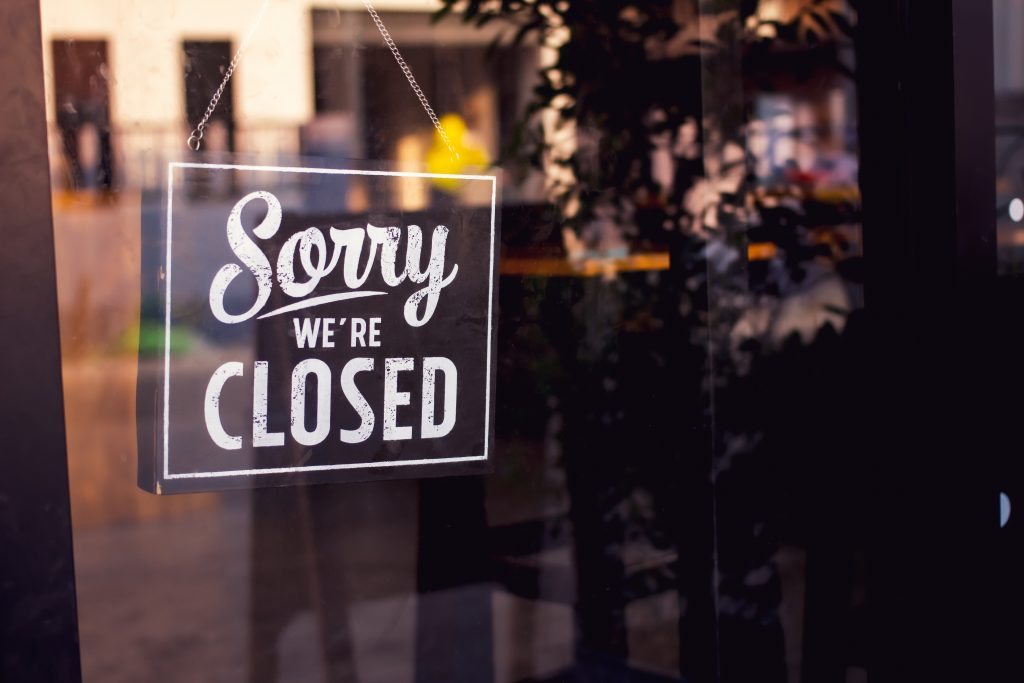 """Vintage """"Sorry, we are closed"""" sign hanging on a glass restaurant door."""