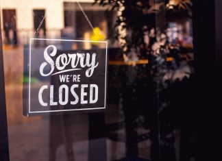 "Vintage ""Sorry, we are closed"" sign hanging on a glass restaurant door."