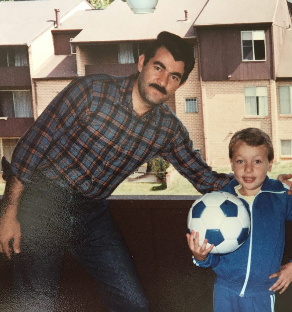 Heart Ball chair Ahmed Elmouelhi as a young child holding a soccer ball and posing with his father