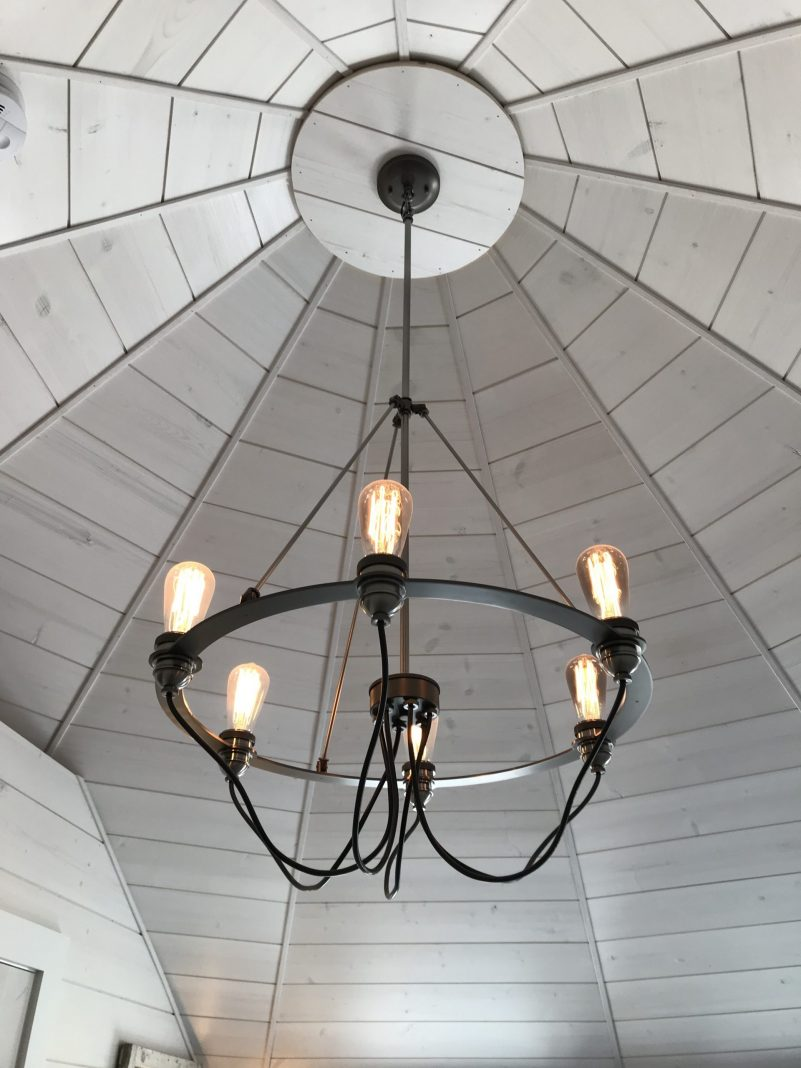 Has there been a more perfect ceiling for a chandelier? This streamlined industrial version ties the room together.