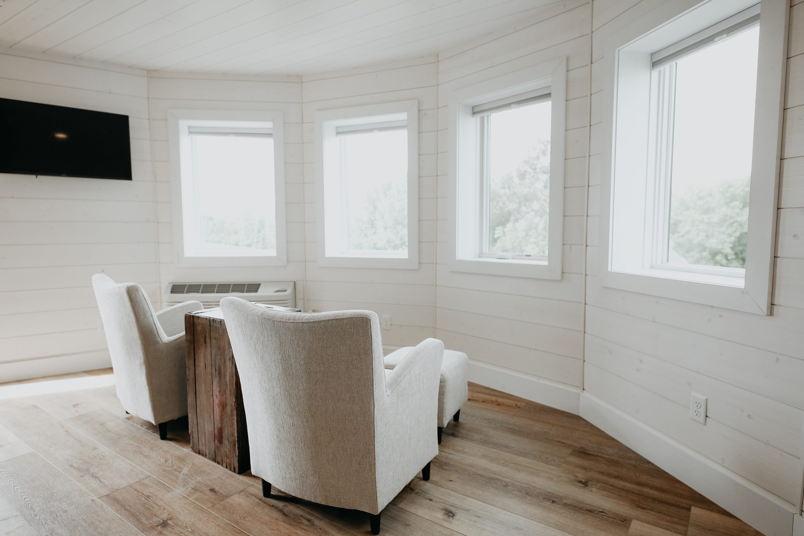 You enter into a small, circular (obviously) room, with chairs oriented toward not the flat-screen TV but the windows, which look out over a small lake, a tiny shed, and conifers.