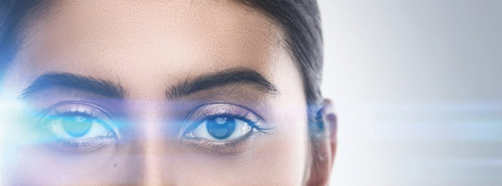 Indian woman in light of optical flares. Concepts of laser eye surgery or visual acuity check-up