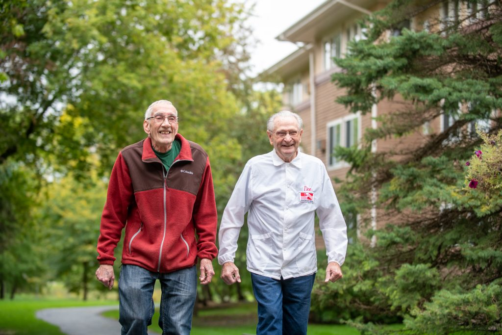 Two elderly males walking outdoors at a SilverCrest assisted living facility.
