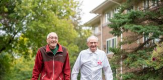 Two elderly males walking while smiling.