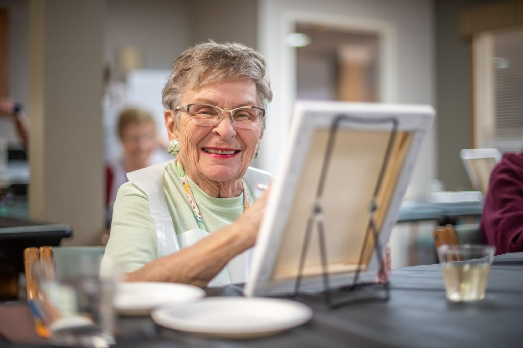 An elderly woman painting at a SilverCrest assisted living facility.