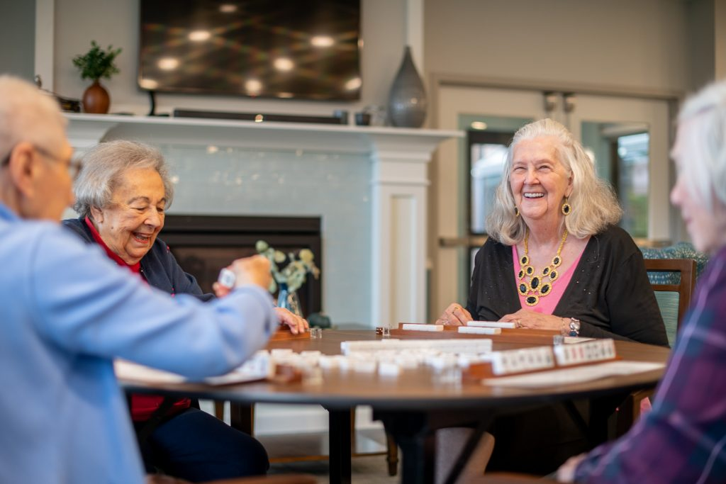Three elderly females playing a board game at a SilverCrest assisted living facility.