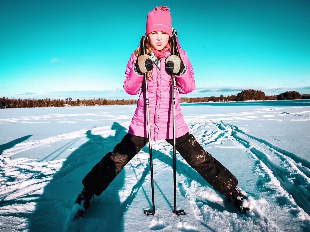 Young girl wearing pink coat and hat looking at camera and holding skiing polls on cross-country skiing trail in Ely, Minnesota