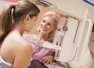 Nurse at Midwest Radiology assisting patient undergoing mammogram smiling