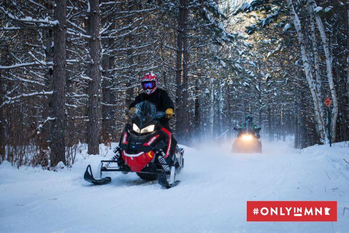 Two people riding snowmobiles on a forest trail in Grand Rapids, Minnesota.