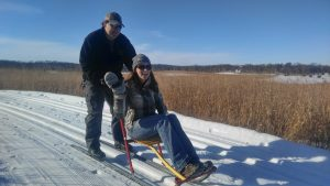 A man giving a woman a ride on a kick sled at Prairie Woods Environmental Learning Center in Willmar Lakes