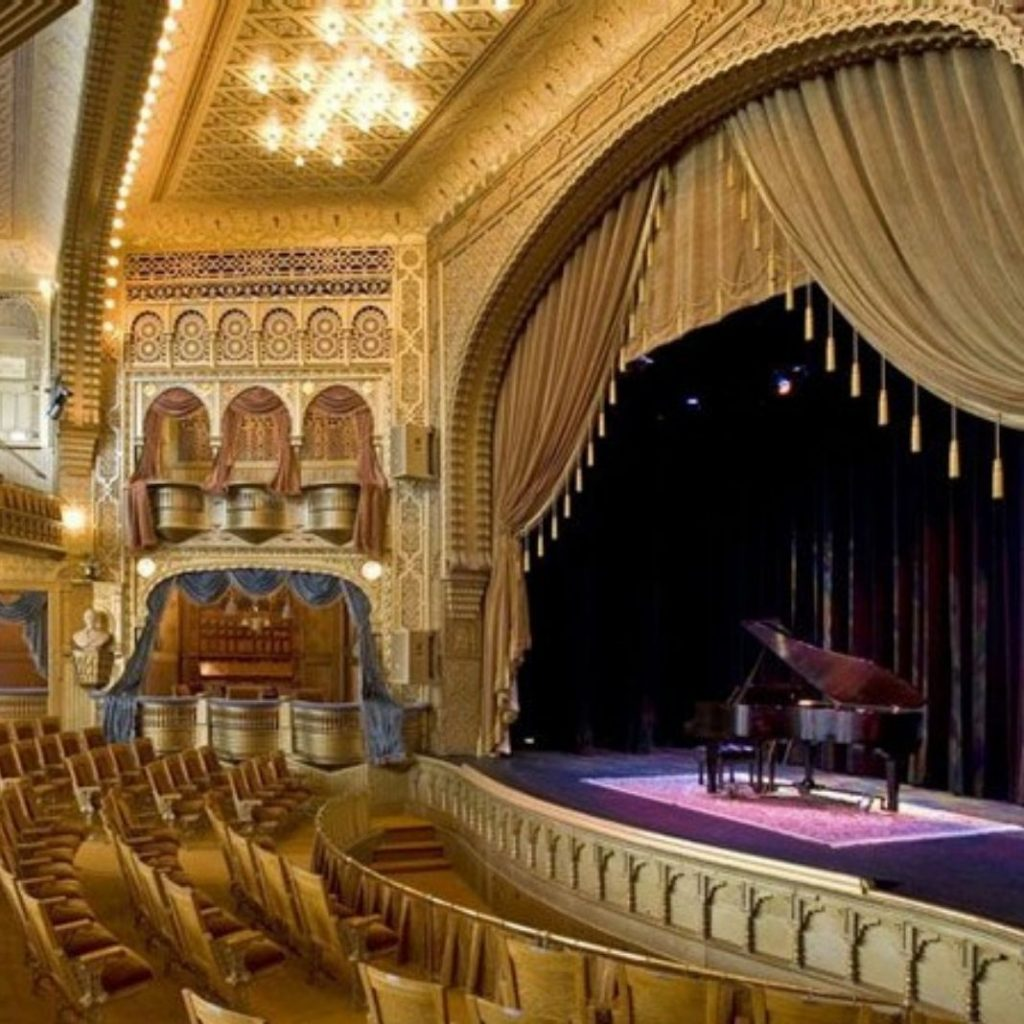 A man playing a piano on stage at the Mabel Tainter Theater in Menomonie, Wisconsin.