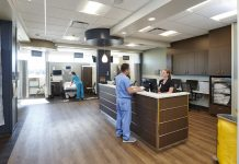 A man and woman wearing scrubs standing at a nurse station at MNGI Digestive Health