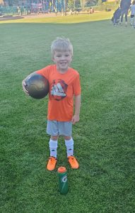 Blonde boy wearing orange shirt and soccer cleats smiling and holding a soccer ball