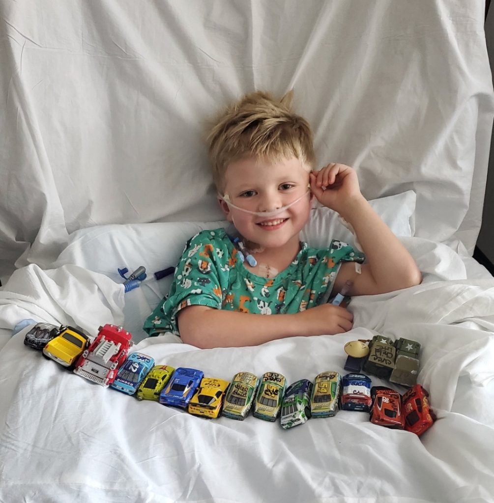 A small boy with blonde hair laying in a hospital bed at Mayo Clinic with toy cars spread out around him