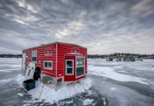 A red fishing hut sitting on a frozen lake in the Willmar Lakes Area