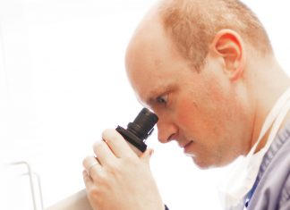 A doctor from Dermatology Consultants looking through a microscope.