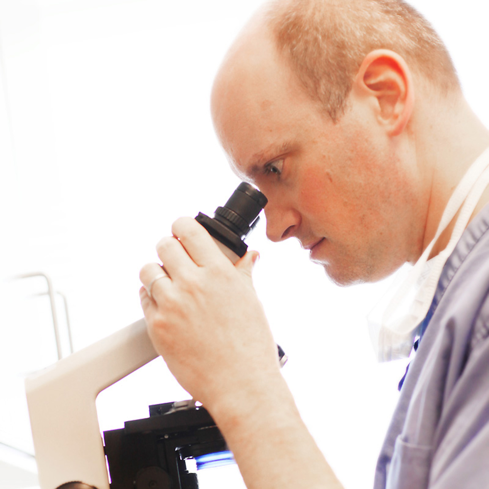 A doctor from Dermatology Consultants looking through a microscope performing phase two of Mohs surgery.