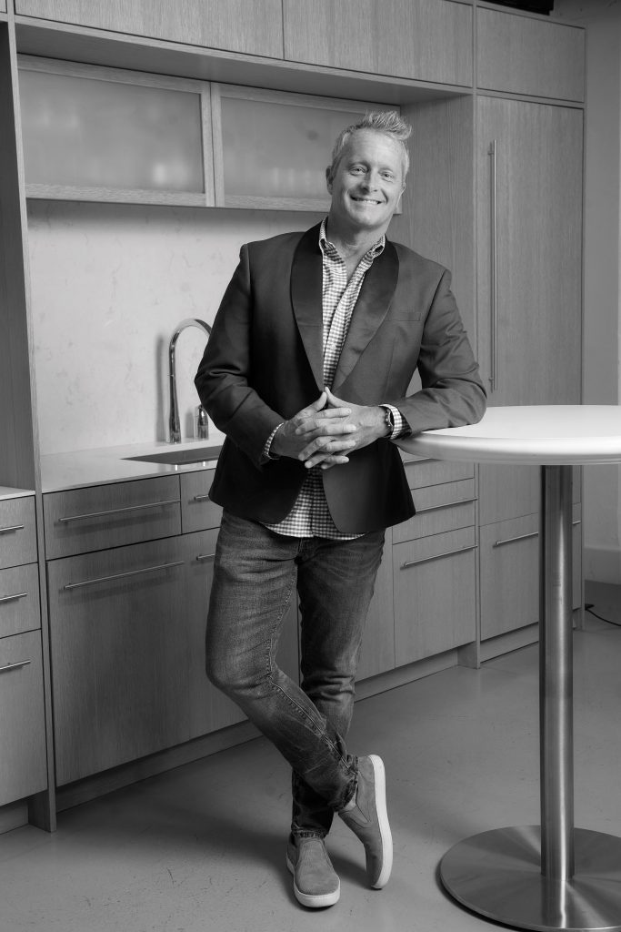 Jon Coty, general manager of Dwell44, leaning against a table in his showroom