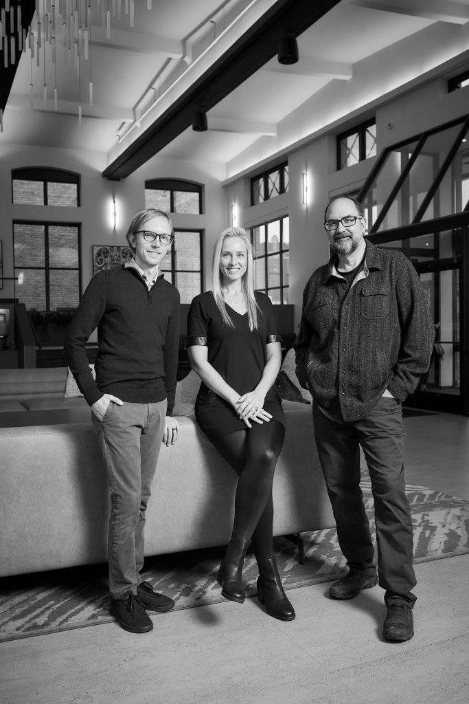 Rob Hull, Angela Liesmaki, and Jim McNeal of James McNeal Architecture stand in the lobby of International Market Square in Minneapolis