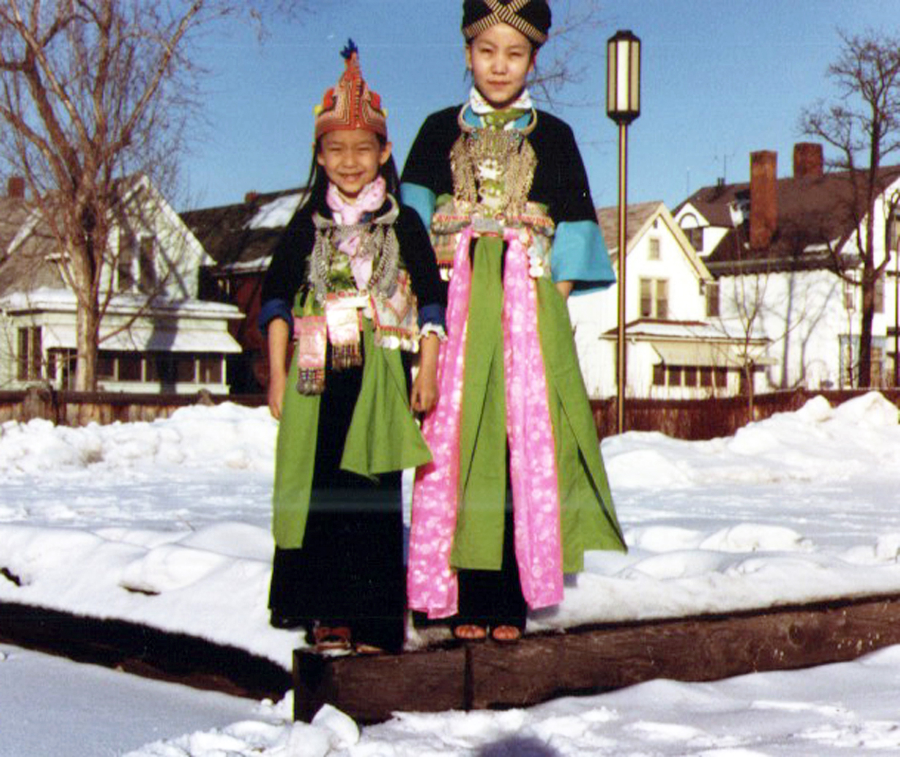 """My sister and me back in the '80s (I am the little one),"" Bidania tells me. ""This was taken outside our house in St. Paul on my family's way to the Hmong New Year celebration. """