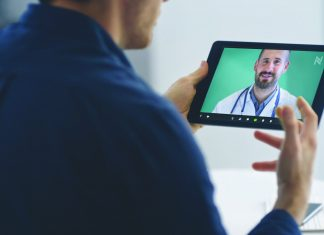 Man holding tablet talking to North Memorial doctor