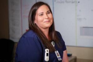 UND student Amy Joshua smiling and wearing nursing scrubs