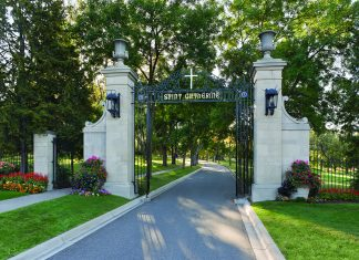 Sun shining through front Gates of St. Catherine University with lots of beautiful trees and flowers