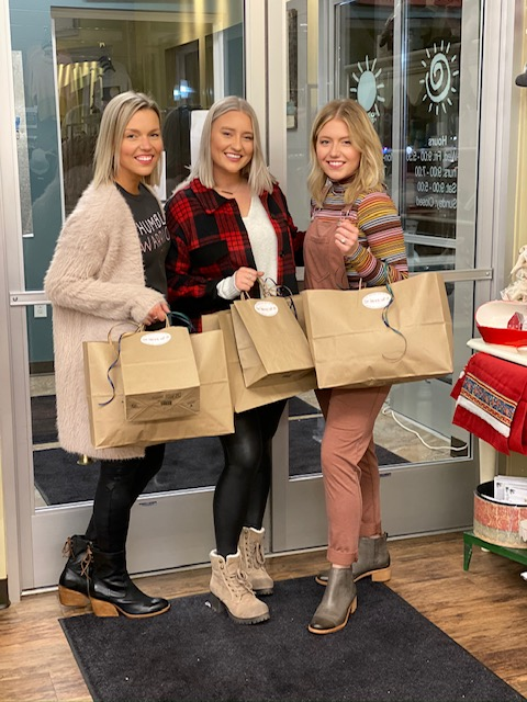 Three women holding shopping bags in New London, Minnesota.