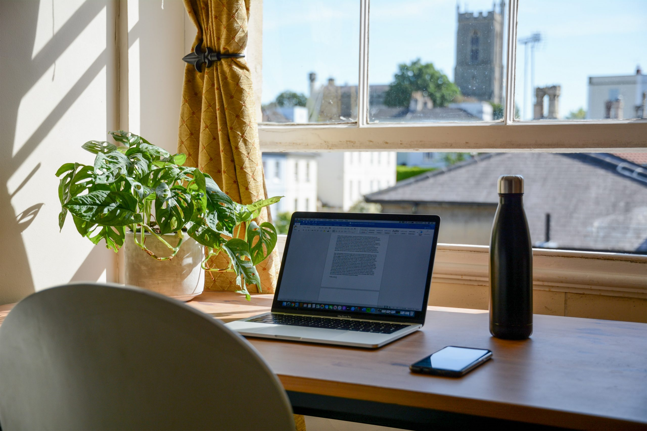 A home office set-up, with a laptop on a table near a window