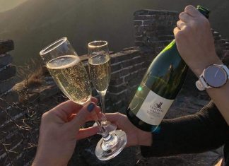 Two hands holding champagne flutes and bottle