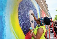 Dr. Eboni Bell painting a community mural at Springboard for the Arts