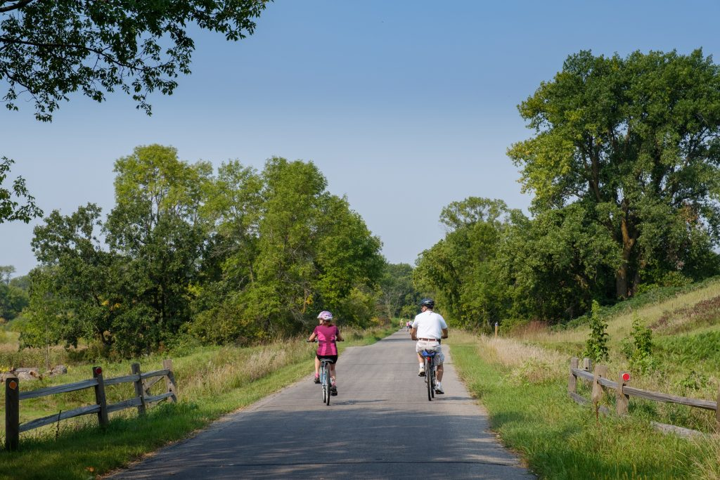 A man and a women biking on the Central Lakes Trail
