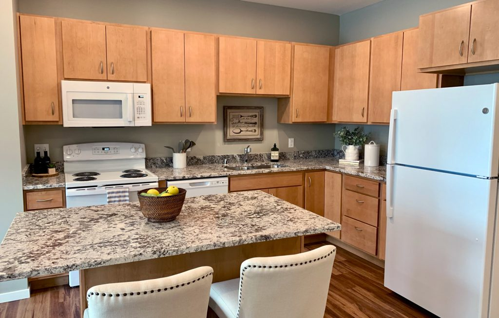Island kitchens with granite countertops at Bren Road Station Apartments