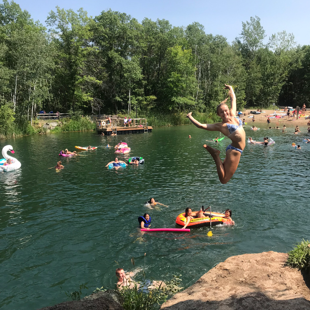 A girl jumping into the water at Quarry Park & Nature Preserve