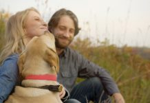 A couple and their dog sitting on the grass in Red Wing, Minnesota