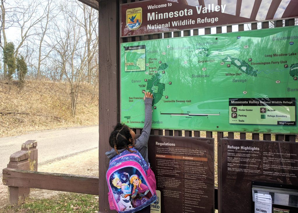 A child viewing a map at the TNC Preserves
