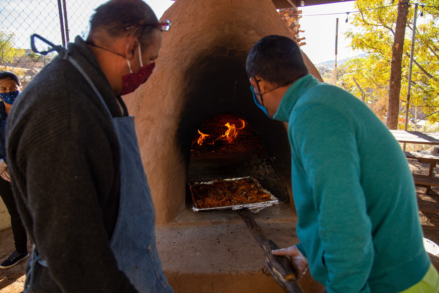 Two people cook in the adobe ovens