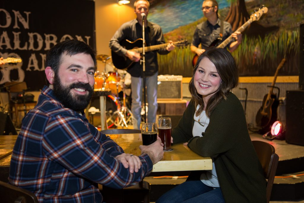 Two people enjoying live music at Klocklow Brewing Company in Grand Rapids